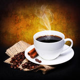 Coffee cup with saucer and coffee beans on burlap over dark Royalty Free Stock Photography