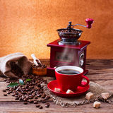 Coffee cup and saucer, coffee grinder, coffee beans in sack and spilled on wooden table. Stock Photography