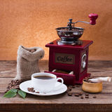 Coffee cup and saucer, coffee grinder, coffee beans in sack and spilled on wooden table. Stock Photo