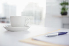 Coffee cup and saucer on desk. In an office royalty free stock images