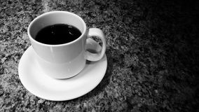 Coffee cup and saucer. On granite in black and white Stock Photo