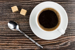 Coffee in cup on saucer, lumpy sugar and spoon Royalty Free Stock Photos