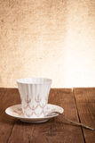 Coffee cup and saucer on a old wooden table. Burlap background Royalty Free Stock Image