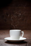 Coffee cup and saucer on old wooden table. Stock Photos