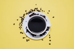 Coffee cup and saucer with spilled coffee beans. On a bright yellow background shot from above Stock Photography