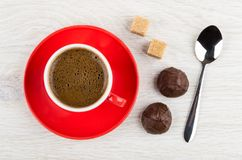 Coffee in cup on saucer, spoon, sugar cubes, chocolate candy. Coffee in red cup on saucer, spoon, sugar cubes, chocolate candy on wooden table. Top view Stock Images