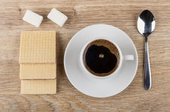 Coffee in cup on saucer, spoon, wafers and lumpy sugar. On wooden table. Top view Royalty Free Stock Image