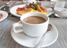 Coffee cup and saucer on table Stock Images
