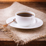 Coffee cup and saucer on tablecloth on wooden table. Dark background. Coffee concept. Selective focus. Stock Images