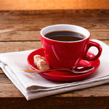 Coffee cup and saucer on tablecloth on wooden table. Dark background. Coffee concept. Selective focus. Stock Photos