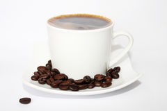 Coffee. A Cup of coffee on saucer on white background with roasted coffee beans royalty free stock photos