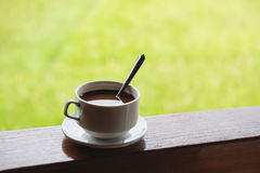 Coffee cup with saucer, on wood panel with defocus green grass lawn background Royalty Free Stock Image
