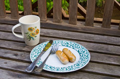 Coffee cup and sausage on plate. With fork and knife ,Wooden chair background Royalty Free Stock Images