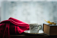 Coffee cup with scarf and old book Royalty Free Stock Images