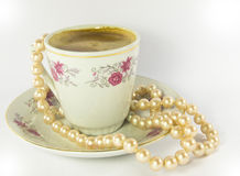 Coffee cup with sea perls necklace. A small espresso coffee with a sea pearls necklace Royalty Free Stock Images