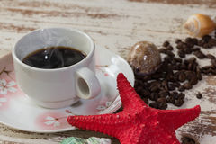 Coffee in cup with sea shel. L and coffee beans on dirty wood table Stock Images
