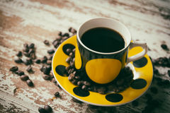 Coffee in cup with sea shel. L and coffee beans on dirty wood table Stock Photo