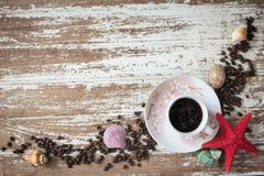 Coffee in cup with sea shel. L and coffee beans on dirty wood table Stock Photography