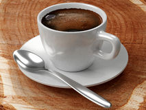 Coffee cup set on a stump. Black coffee with froth in a white porcelain cup, saucer of same material, and a silver spoon, all on a table made of a tree stump Stock Photo