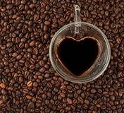 Coffee cup in the shape of heart on coffee beans background. Top stock photos