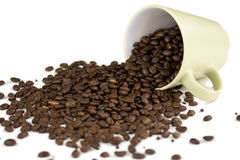 Coffee Cup On Side. A coffee cup filled with whole coffee beans turned over and spilled out Stock Images