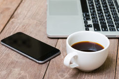 Coffee cup smart phone and laptop. On old wooden table stock images