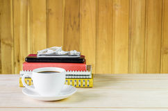 Coffee cup,smart phone and note book on wooden table Royalty Free Stock Photo
