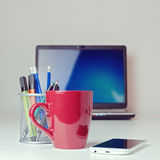 Coffee cup with smart phone on office desk royalty free stock image