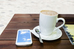 Coffee cup and  smart phone. Coffee cup on table and smart phone Royalty Free Stock Image