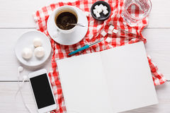 Coffee cup and smartphone on checkered cloth at white wood Stock Photo