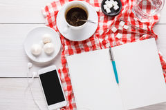Coffee cup and smartphone on checkered cloth at white wood Royalty Free Stock Photo