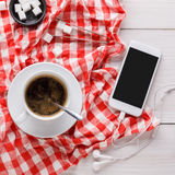 Coffee cup and smartphone on checkered cloth at white wood Royalty Free Stock Photos