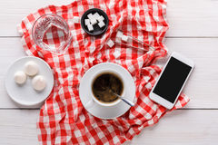 Coffee cup and smartphone on checkered cloth at white wood Stock Images