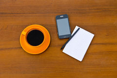 Coffee cup with smartphone, notepad and pen on wooden desk Stock Image