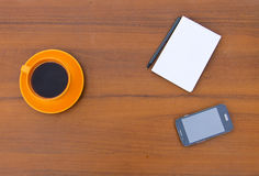 Coffee cup with smartphone, notepad and pen on wooden desk Royalty Free Stock Image