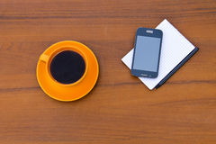 Coffee cup with smartphone, notepad and pen on wooden desk Stock Photos