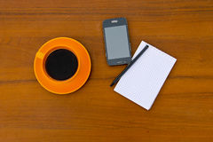 Coffee cup with smartphone, notepad and pen on wooden desk Royalty Free Stock Images