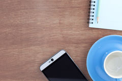 coffee cup with smartphone ,paper note and pencil on wood table Royalty Free Stock Photo