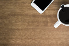 Coffee Cup and Smartphone on Wooden Desk Top View Royalty Free Stock Image