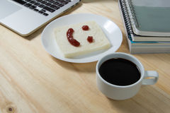 Coffee cup and smile on bread, made of strawberry jam. Closeup coffee cup and smile on bread, made of strawberry jam Stock Photos