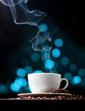 Coffee cup with smoke and abstract bokeh Stock Images