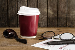 Coffee cup ,Smoke pipe ,glasses,pen and Paper on wood Table : Still Life Royalty Free Stock Image