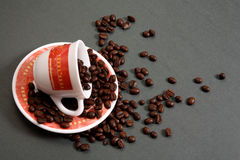 Coffee cup spilling beans. Coffee cup on side spilling dark roasted beans, studio background Stock Photography