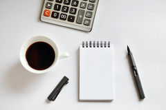 Coffee cup, spiral notebook, calculator, and pen on white backgr Royalty Free Stock Photo