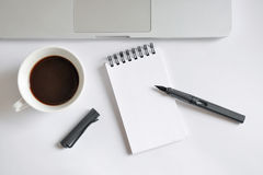 Coffee cup, spiral notebook, computer keyboard, and pen on white Royalty Free Stock Photography