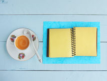 Coffee cup and spiral notebook on a painted wood background Stock Photos