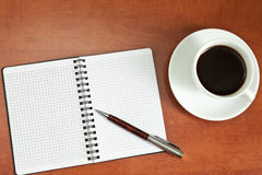 Coffee cup, spiral notebook and pen Stock Photography