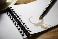 Coffee cup, spiral notebook and pen Stock Image