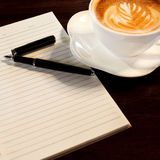 Coffee cup, spiral notebook and pen Royalty Free Stock Photos