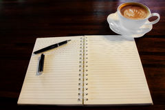 Coffee cup, spiral notebook and pen Royalty Free Stock Images